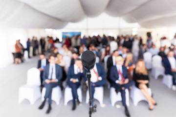 Business conference. Corporate presentation. Microphone in focus against blurred audience.
