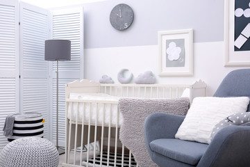 Baby bedroom design with white crib and armchair