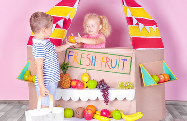 Little children playing with cardboard stall on color wall background
