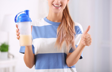 Young woman holding bottle with protein shake indoors