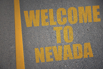 asphalt road with text welcome to nevada near yellow line.