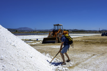 Tourist photographed  jokingly while sinking a shovel into a pool of sea salt in a saline