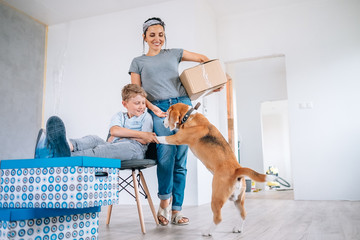 Happy family move in new apartment - mother, son and  beagle
