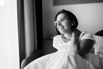 Happy smiling woman in eyeglasses meets new day in bedroom