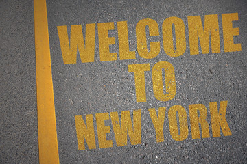 asphalt road with text welcome to new york near yellow line.