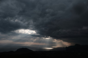 ominous clouds and the bursting rays of light over the gulf sea