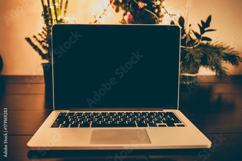 Laptop computer with blank screen on wooden table with Christmas tree and Christmas  lights on background - Laptop Computer With Blank Screen On Wooden Table With Christmas