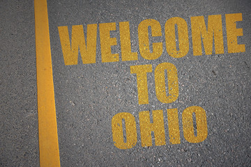 asphalt road with text welcome to ohio near yellow line.