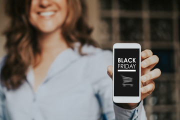 Black Friday shopping app in a mobile phone screen, while smiling woman holds it in the hand