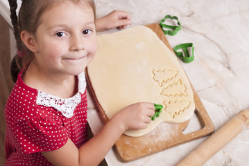 little girl is cooking gingerbread