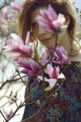 Beautiful redhead girl in pink spring flowers