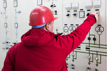 Engineer with red helmet give command in power plant control center