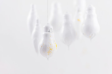 White light bulbs with yellow spray on a white background