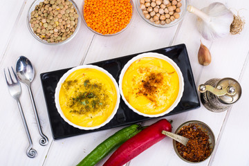 Two bowls with homemade hummus on white wooden background