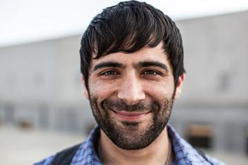 A man with dark hair and beard smiling looking at camera