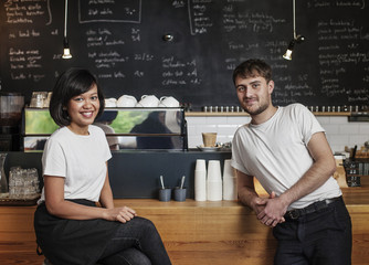 Portrait of two young business owners in a Cafe.