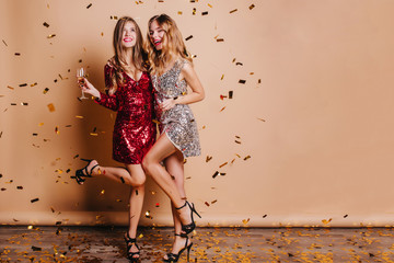 Full-length portrait of happy girls wears high heel shoes dancing at party under confetti. Indoor photo of funny ladies chilling at home during christmas celebration and drinking champagne.