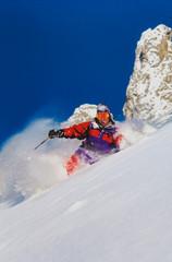 Young man in orange jacket skiing in powder snow in St Anton Austria