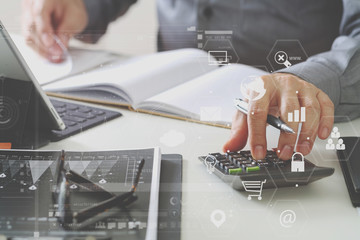 businessman hand working with finances about cost and calculator and latop with mobile phone on withe desk in modern office