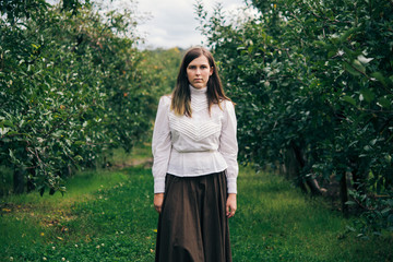 Teen Girl Standing in Apple Orchard