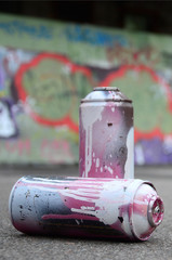 A few used spray cans with pink and white paint lie on the asphalt against the background of a painted wall in colorful graffiti drawings