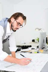 handsome young trendy man working in architect office creative activity