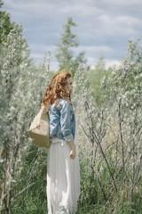 Beautiful young redhead woman walking in nature