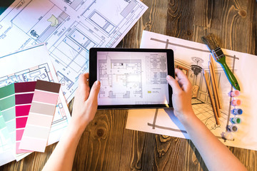 Flatlay interior designer with tablet pad and plans and art tools