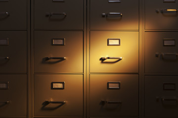 Spotlight shining on a wall of metal filing cabinets
