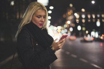 Woman Texting on the Street at Night