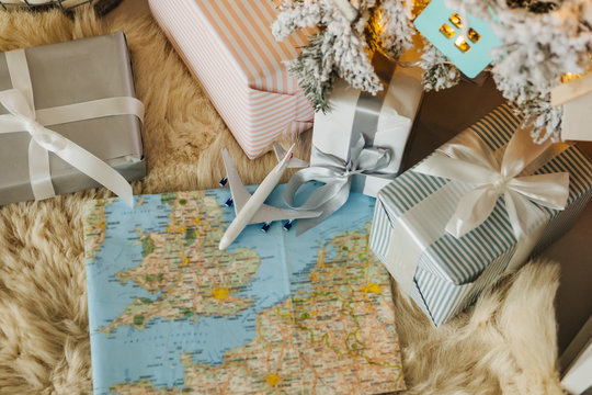 Airplane is on the map among the New Year's Christamas gifts under the tree. Give a trip. Top view.