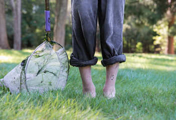 Muddy, wet child with rolled up pants and a net stands in the grass