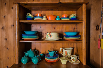 Colorful Antique Dishes in a Wooden Hutch