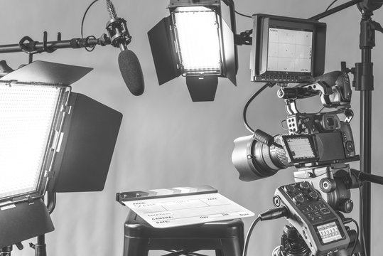 Professional video camera, lights and microphone equipment all set up for an interview in a studio setting.