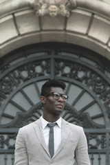African young businessman with rimmed glasses in outdoors.