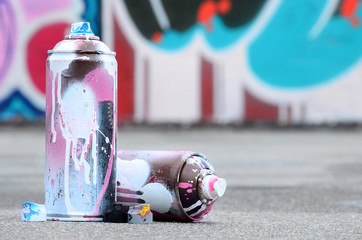 In de dag Graffiti Several used spray cans with pink and white paint and caps for spraying paint under pressure is lies on the asphalt near the painted wall in colored graffiti drawings