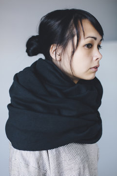 A profile of a young asian woman in a big scarf