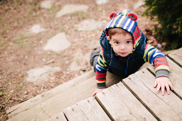 A toddler climbing the stairs on a deck in the spring.