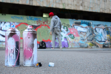 Several used spray cans with pink and white paint lie on the asphalt against the standing guy in front of a painted wall in colored graffiti drawings