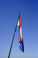 A  dutch flag in a windless sky, in the Netherlands