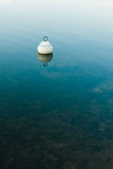 Wooden buoy floating on water surface