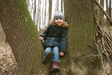 Little girl sits on a tree in a forest smiling happily.