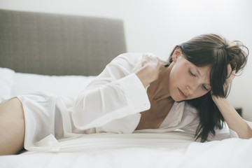 A beautiful woman lying in bed adjusting her collar