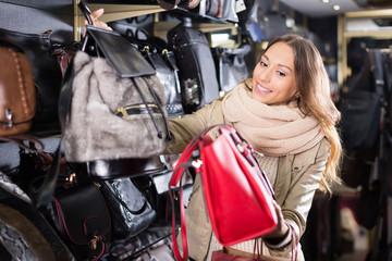 Ordinary girl choosing bag among assortment