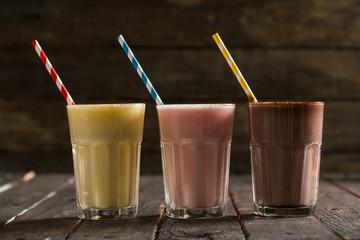 Fotobehang Milkshake Delicious Milkshakes on Wooden Background