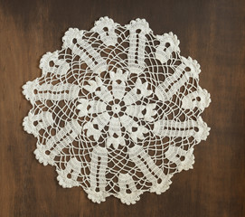 Round vintage crochet doily on dark background
