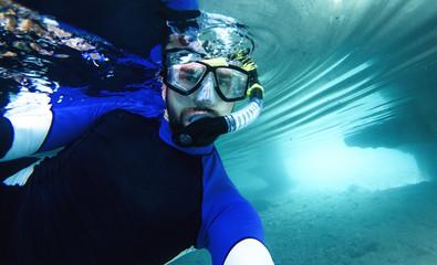 Junger Mann macht Selfie beim Schnorcheln in einer Höhle