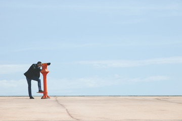 Young businessman looking with red telescope in front of blue sky.