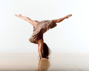 Female dancer gymnast balancing on two hands while doing the splits in the air