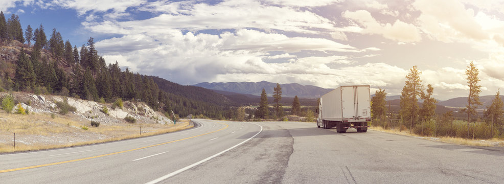A panorama of beautiful mountainous landscape with a highway running through it and a 18-wheeler stopped on the shoulder